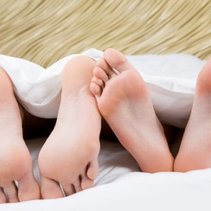 Image of two pairs of bare male and female feet located in opposite direction